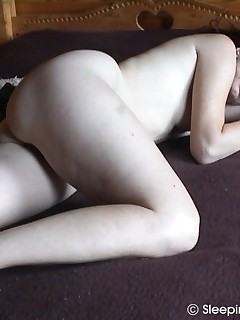 Brunette middle-aged woman filmed in nude sleep